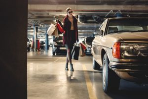 Woman carrying shopping bags to car in parking garage